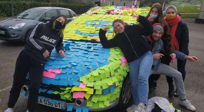 Une voiture multicolore sur le parking du lycée